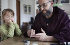 A dad checks his blood with a diabetic testing kit while his daughter watches, confused.