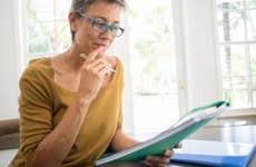 Woman reading folder at desk in living room