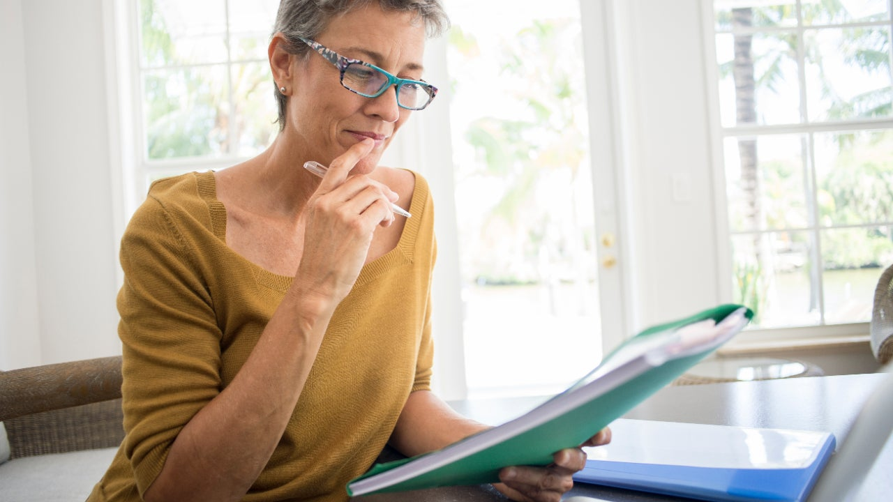Woman reading folder at desk in living room