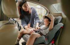 Asian mother buckling her young son into his car seat.