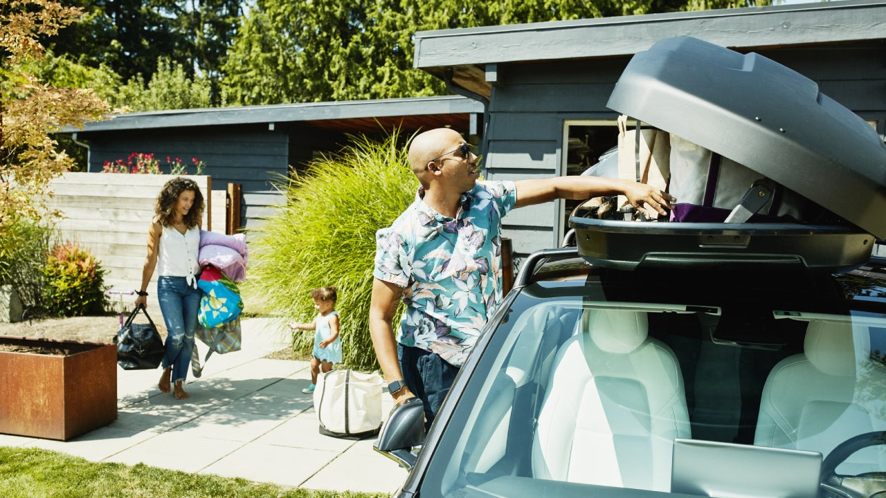 A family is loading up the car for a family trip.