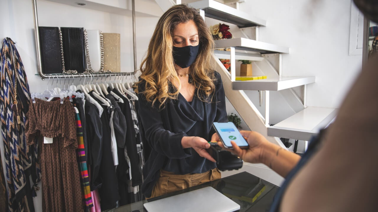 Woman at checkout counter taking credit card payment