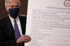 Sen. Angus King (I-ME) sets up a sign alongside a bipartisan group of Democrat and Republican members of Congress as they announce a proposal for a Covid-19 relief bill.