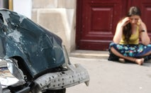 A woman sits on the sidewalk on her smartphone next to her car that has been hit.