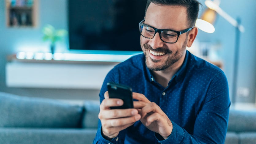 A man smiles while looking at his phone