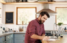 Man working on laptop in kitchen