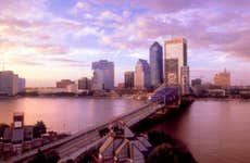 Skyline of Jacksonville, Florida with the sky turning purple and the sun setting.