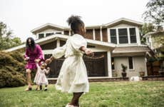 African American mother and her two daughters playing on the front lawn of their beautiful home.