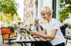 A White woman holds her phone at an outdoor cafe