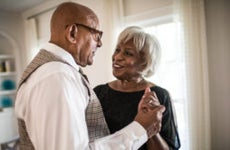An older Black couple dances in their living room