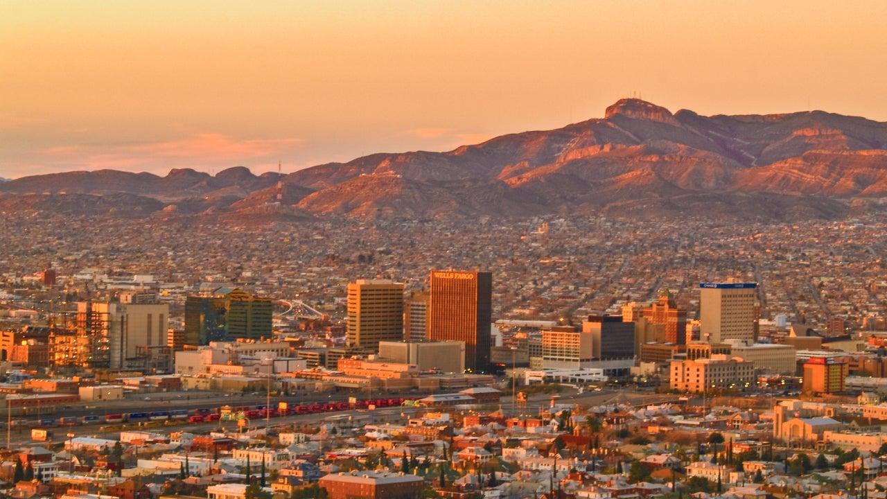 City skyline against an orange sky of a setting sun.
