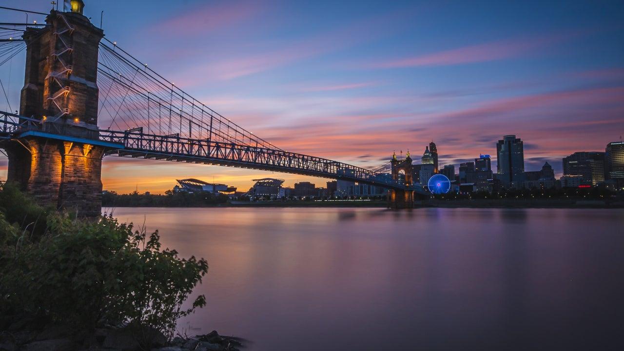 Bridge outside of Cincinnati at nightfall with a Ferris wheel lit.