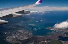 A Hawaiian Airlines plane flying over Honolulu.