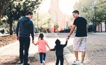 A gay couple walks with their kids.