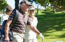 An older White couple plays golf together