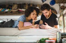 A couple looks at a phone in their camper van