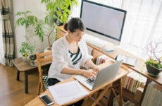 An Asian-American woman trads stocks from her home office computer