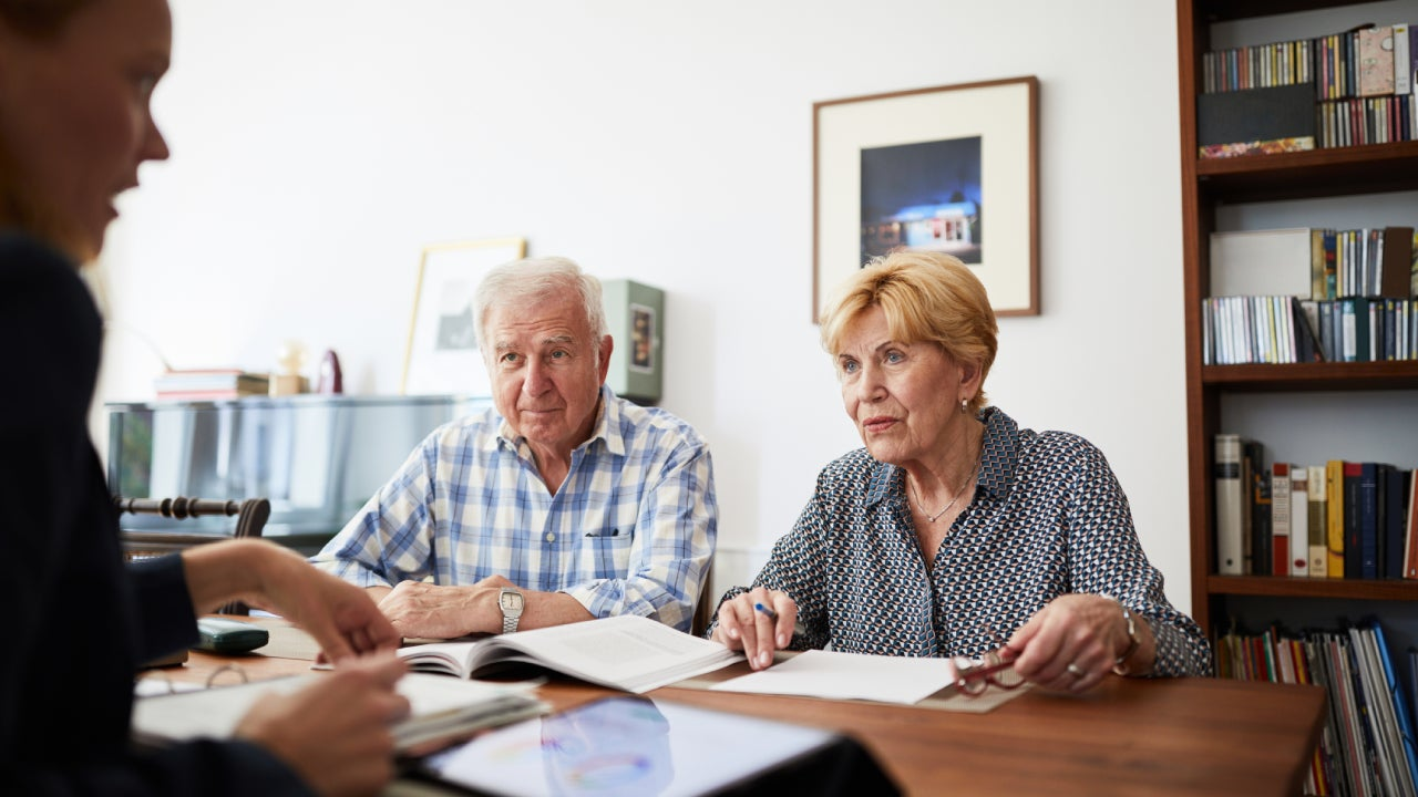 An older couple sits at a desk across from an insurance expert.