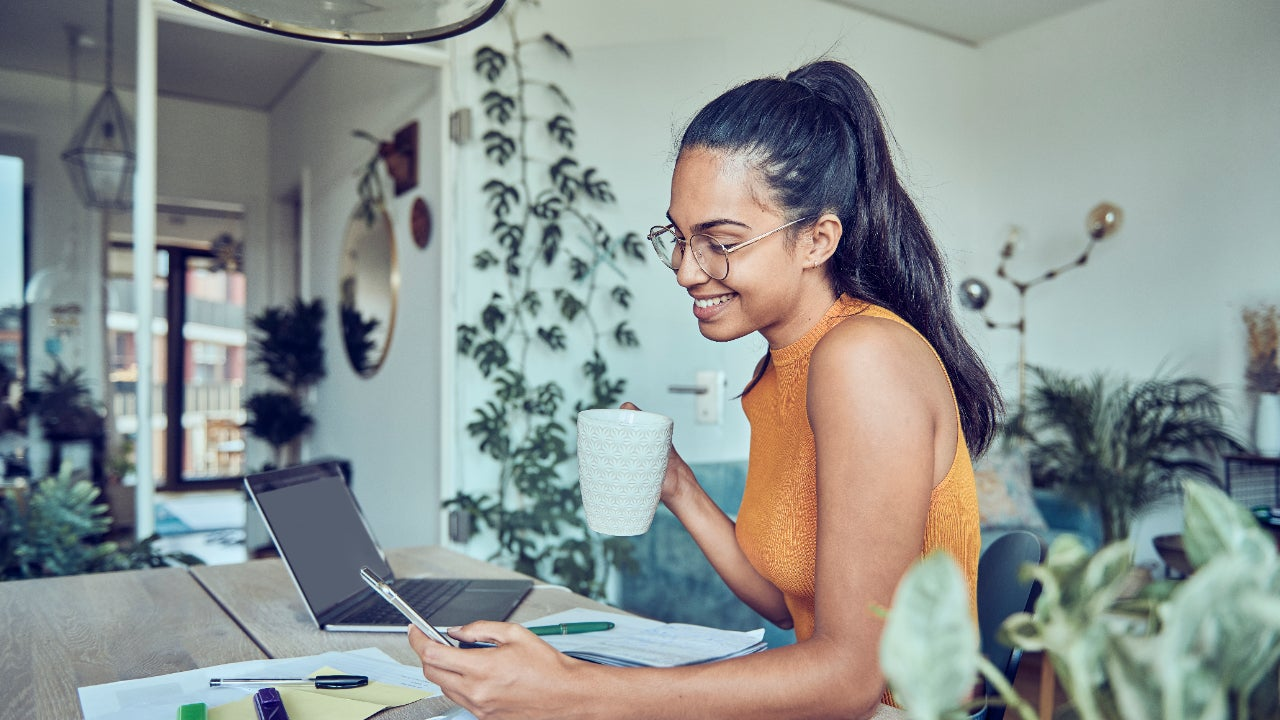 A young woman checks her phone while at her desk at home