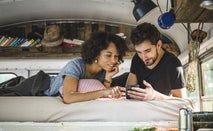 A young man and woman are in the bunk of their Winnebago looking on the phone at possible insurance options.