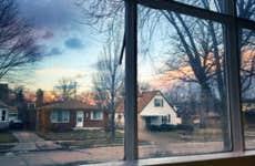 Suburban houses seen through a window at sunset.