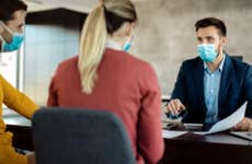Young couple meets with a mortgage banker. Everyone is wearing face masks.