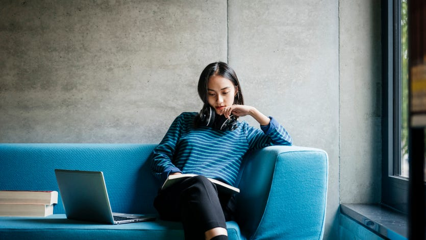 A young woman sitting on a couch looking at a laptop in a quiet library space