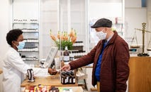 Senior man with mask giving prescription to female pharmacist in store.