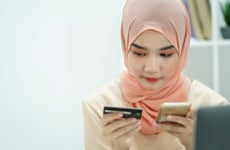 Person looking at credit card and cellphone