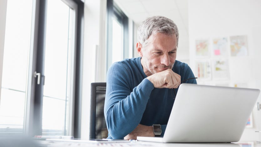 An older White man sits at a laptop computer on his desk