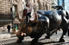 A man sits astride the bull in front of the New York Stock Exchange