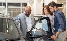 Couple looks at a car at a dealership