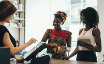 Two women paying a female cashier in a store