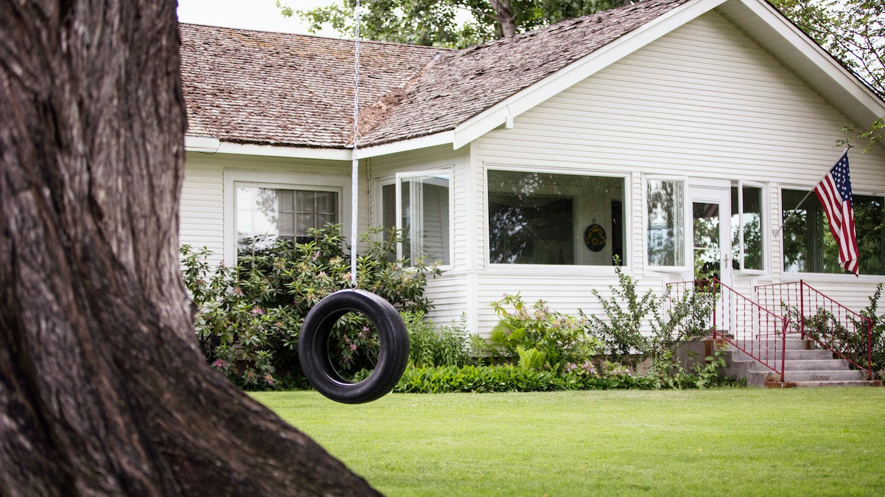 House with tire swing, American flag