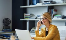 A young White businesswoman at her desk on the phone