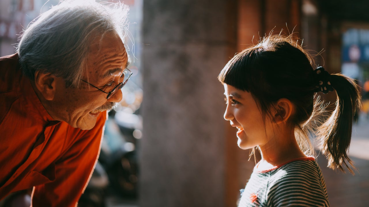 Asian grandpa bending low to speak with his young grand daughter. They are laughing together.