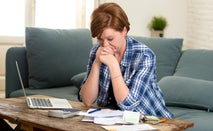 Woman looks through bills and paperwork