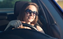 Woman wearing sunglasses drives a car