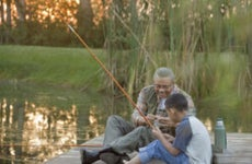 Black senior and his grandson are sitting together on a dock with fishing rods laughing together.