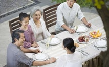 Extended Asian family sitting together outdoors enjoying a meal.