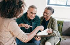 A Black financial advisor shows a Black couple a legal document