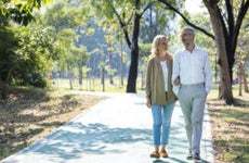 Older couple walking together in a park.