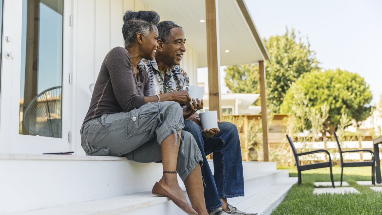 Older black couple sitting on the porch steps of their home with coffee, enjoying the day.