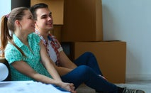 Couple sits in new home with moving boxes