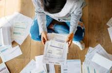 Person looks through bills on the floor