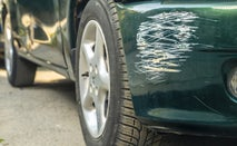 Close-up of a green car with a scratched fender where a white car hit it.