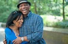 A middle-aged Black couple holds one another laughing in front of a park