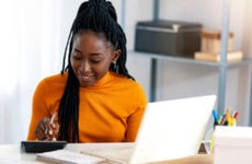 A Black woman using a calculator.