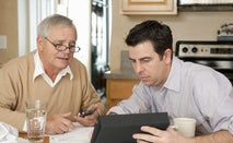An old man sits with an insurance adjustor to go over some details.