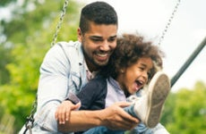 An African-American father playing with his little daughter on a swing set.